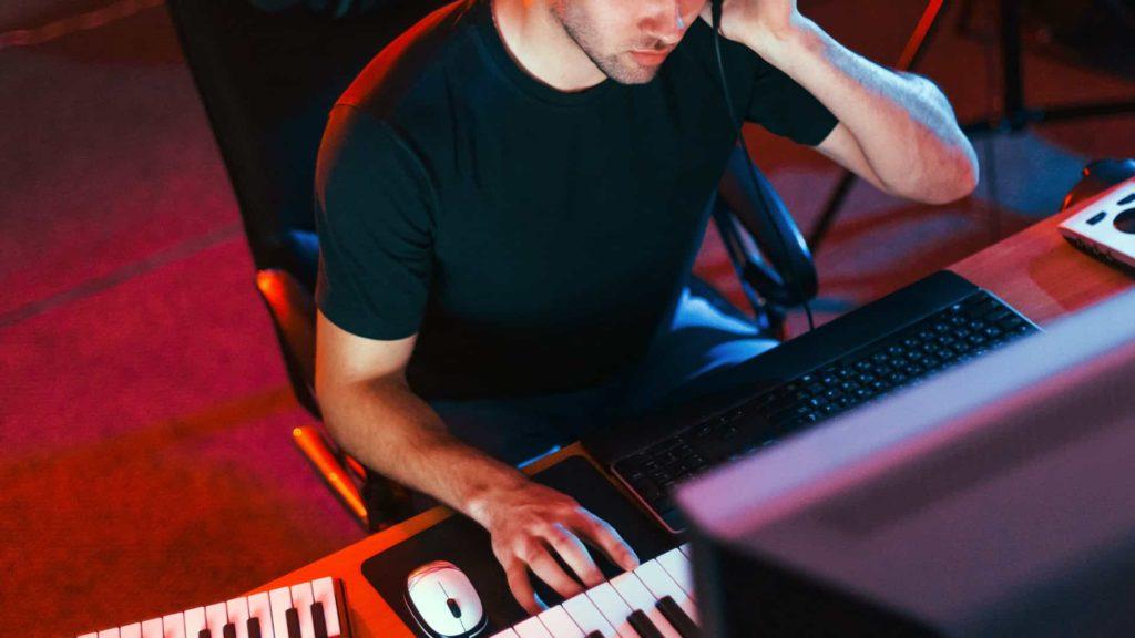 Producteur musical en train de produire de la musique sur Synthé et ordinateur